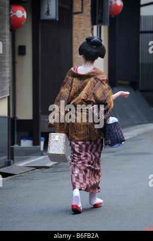 A Maiko, a trainee Geisha, walking in the Gion Quarter on her way to Odori, Kyoto, Japan, Asia - Stockfoto