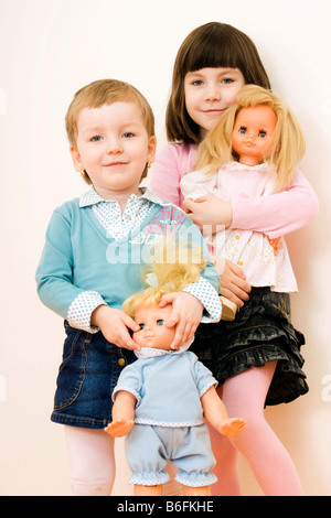 Two little girls, 3 and 6 years old, with dolls, indoors - Stock Photo
