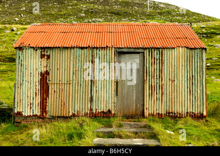 Wriggly Tin shack, corrugated iron building in Tarbeart Lewis Scotland showing age and colour - Stock Photo