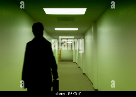 businessman with briefcase walking down empty corridor - Stock Photo