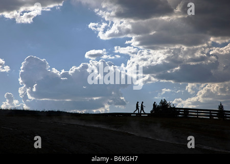 Visitors silhouetted and dramatic sky, Grand Prismatic Spring, Midway Geyser Basin, Yellowstone National Park, Wyoming, - Stock Photo