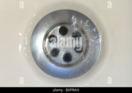 water running down a plug hole in domestic bath. Slow shutter speed and flash effect - Stock Photo