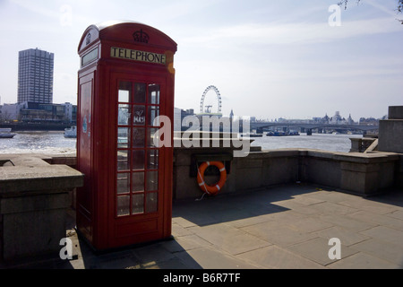 Traditional British red telephone box along the North embankment of the River Thames with the London Eye beyond. - Stock Photo
