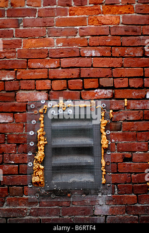 A covered vent on the side of a brick building in Boston Mass - Stock Photo