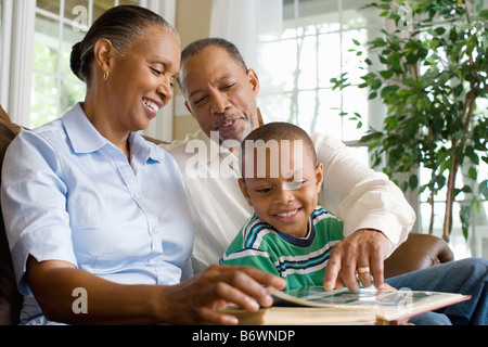 Grandparents and their grandson looking at a photo album - Stock Photo