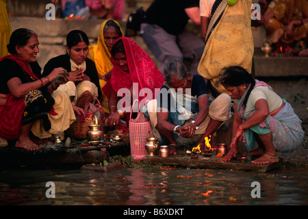 india, varanasi, ganges river, women giving offerings at dawn - Stock Photo