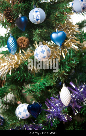 Christmas decorations, paper and metallic with tinsel, on Christmas tree - Stock Photo