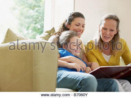 Family looking a photograph album - Stock Photo