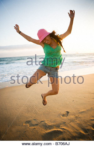 A smiling woman jumps into the air and clicks her heels together on the beach on a sunny summer evening. - Stock Photo