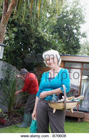 Senior woman holding gardening basket - Stock Photo