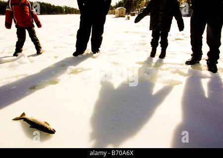 People ice fishing on Maine Lake in North Waterboro, Maine. - Stock Photo