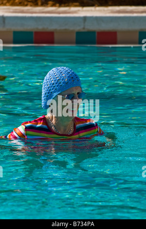 Active senior lady wearing swimming suit stock photo - Palm beach swimming pool ...