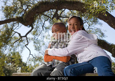 Young African American children outdoors sitting in park - Stock Photo