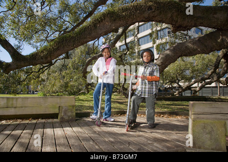 Young African American boy and girl riding scooters in park - Stock Photo