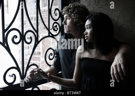 Young interracial couple looking out window - Stock Photo