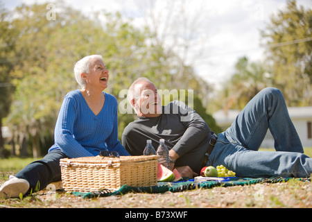 Senior couple having picnic in park, smiling - Stock Photo