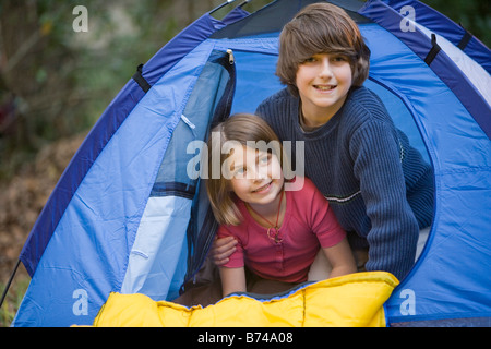 Portrait of brother and sister peaking out from inside tent - Stock Photo