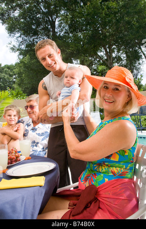 Extended family relaxing in backyard - Stock Photo