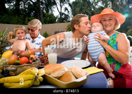 Extended family relaxing by swimming pool - Stock Photo