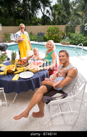 Portrait of three-generation family sitting by swimming pool - Stock Photo