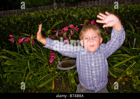 Boy making faces in garden - Stockfoto