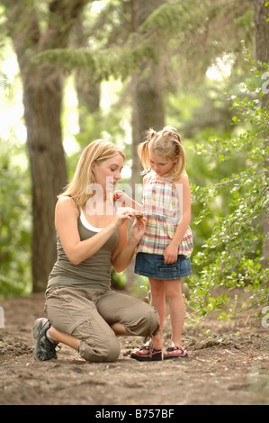 Young woman and child in woods looking at scenery, Regina, Saskatchewan - Stockfoto