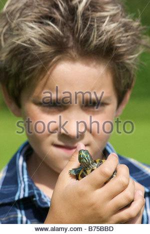 Eight year old boy holding turtle, Winnipeg, Canada - Stock Photo