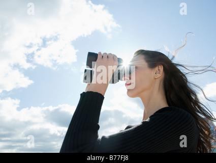 Woman looking through binoculars - Stock Photo