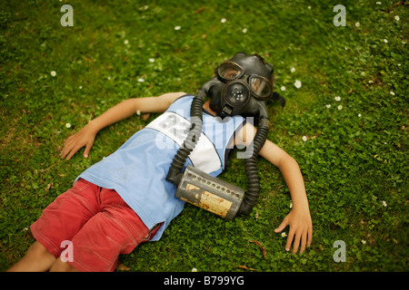 Six year old boy lies on green grass wearing gas mask - Stock Photo