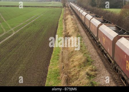 EWS DB Schenker freight train passing Swarkestone Derbyshire heading toward Burton on Trent pulling empty coal wagons - Stock Photo