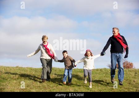 Grandparents And Grandchildren Running In The Park - Stock Photo