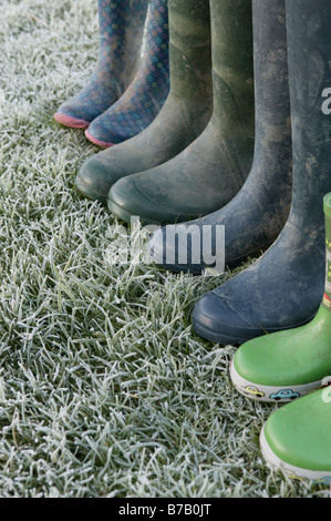 a lineup of a family of wellington boots left on some frosty green grass offering a conceptual image describing - Stock Photo