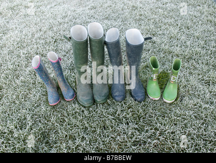 a lineup wellington boots left on some frosty green grass offering a conceptual image describing family structure - Stock Photo