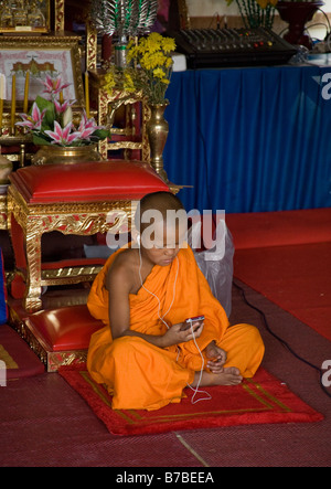 A young novice Buddhist monk listens to an ipod. - Stock Photo