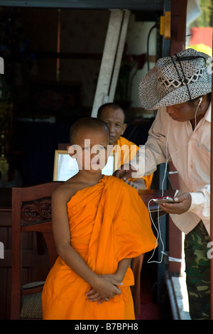 A tourist listening to an ipod is talking a young novice Buddhist monk - Stock Photo