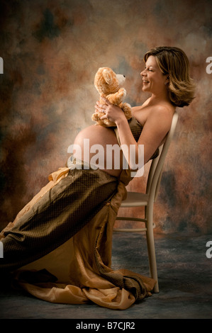 pregnant woman with child's toy sitting in chair - Stock Photo