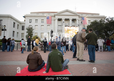 A couple sit on a blanket waiting to watch the inauguration of Barack Obama on the jumbotron at UC Berkeley. - Stock Photo