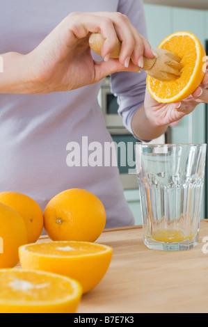Woman making orange juice - Stock Photo