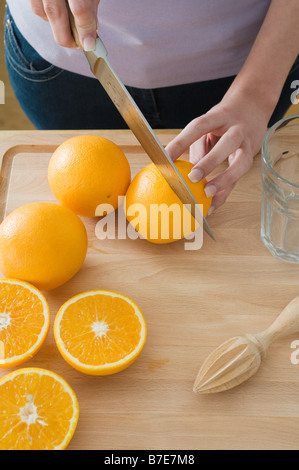 Woman cutting oranges - Stock Photo