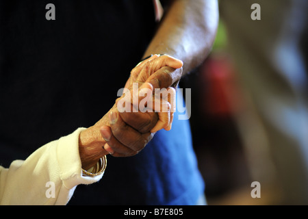 A close up of elderly Sikh ladies hands as she is helped to her chair in a multicultural extra Care home Bradford - Stock Photo