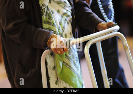 An elderly Sikh lady is helped to her chair in a multicultural extra Care home Bradford West Yorkshire - Stock Photo