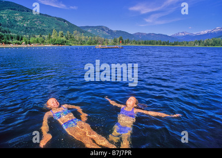 Girls, 10, float in Alta Lake on a sunny summer day - Stock Photo