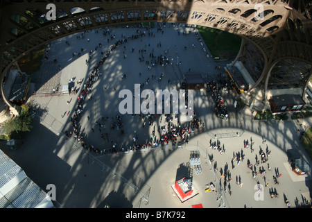 View from first stage of Eiffel tower of visitors queuing for the lifts - Stock Photo