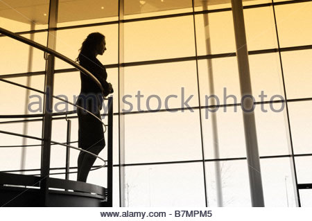 A businesswoman looking over balcony railings in a modern office building - Stock Photo