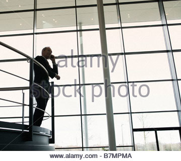 A businessman talking on a mobile phone in a modern office building - Stock Photo
