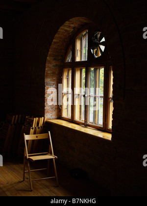 Wooden Folding Chair In A Dimly Lit Room By A Circle Top
