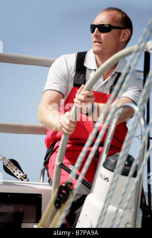 White European male age 20-25 sailing a yacht - Stock Photo