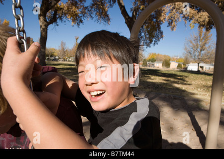 close up of happy nine year old japanese boy swinging on a tire swing at a public park - Stock Photo