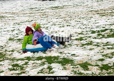 Two young girls having fun sliding down hill in snow UK - Stock Photo