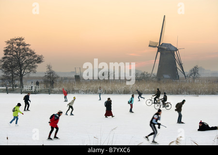 Ice skaters and even cyclists on natural ice in front of a windmill at Kinderdijk Holland, The Netherlands. At sunset. - Stock Photo